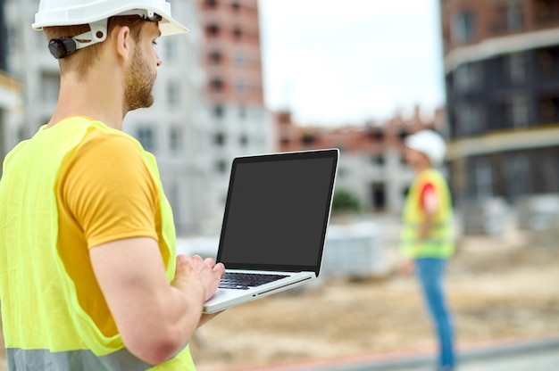 Geschoolde mannelijke arbeider die zijn gadget op de bouwplaats gebruikt