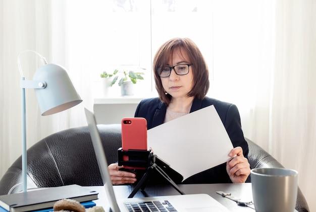 Geschoolde vrouw van middelbare leeftijd online communiceren of studeren op afstand via de telefoon op het statief,