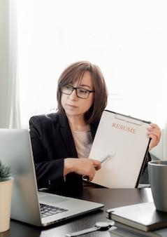 Geschoolde vrouw van middelbare leeftijd online communiceren, studeren op afstand of werken in een wervingsbureau.
