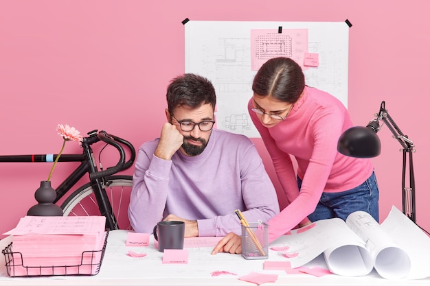 Geschoolde vrouwelijke ontwerper probeert mannelijke collega uit te leggen dat zijn fout wijst op papieren poses in de buurt van desktop. vrouwelijke en mannelijke professionals werken samen aan het ontwikkelen van gemeenschappelijke zoekinformatie voor ontwerpprojecten