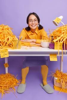 Geschoolde vrouwelijke student werkt aan creatief universitair cursuswerk zit tevreden aan rommelige tafel poseert thuiskantoor draagt nette kleding maakt memo's bereidt zich voor op college-examens geniet van werktijd