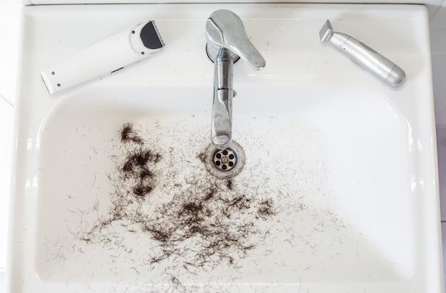 Geschoren haren in de wasbak met scheermesje en trimmer. kapper tools
