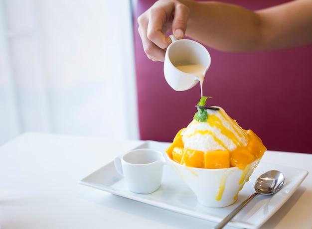 Geschoren ijs, dessert en ijs met het gieten van gecondenseerde melk