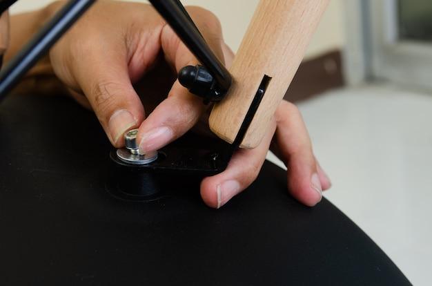 Geschoten close-up, hand van timmermans vastschroevende weg van stoelen