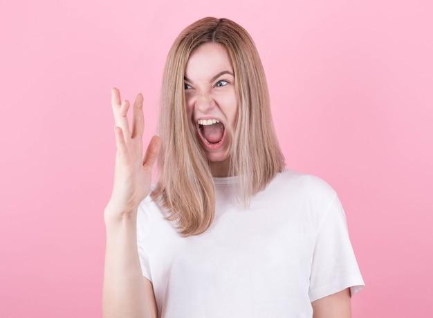 Geschreeuw, haat, woede. emotionele boze blonde vrouw in een wit t-shirt, kijkt naar haar hand op een roze achtergrond.