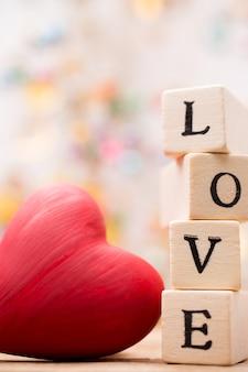 Geschreven op houten blokken liefde en rood hart.
