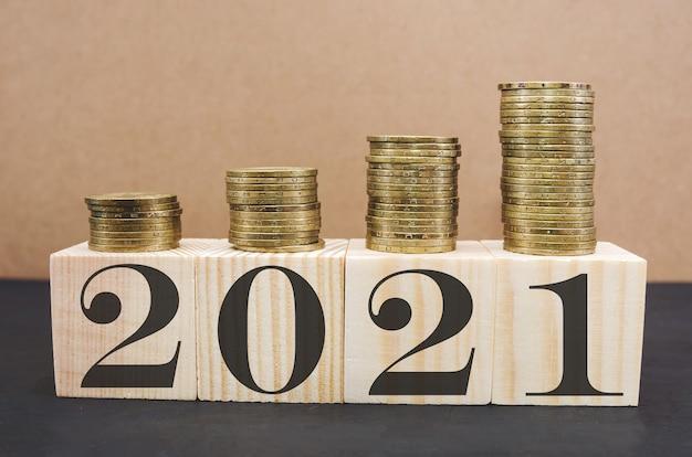 Geschreven op houten kubussen stapels munten in groeiopdrachten financiële planning voor het nieuwe jaar een oplossing om geld te besparen voor de toekomst in zaken of leven