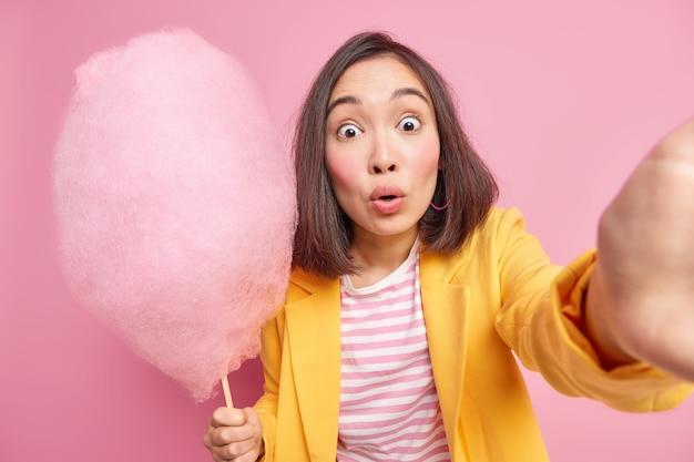 Geschrokken aziatische vrouw staart afgeluisterde ogen maakt foto van haarlef houdt smakelijke suikerspin houdt van iets zoets eten poses tegen roze muur in stijlvolle kleding