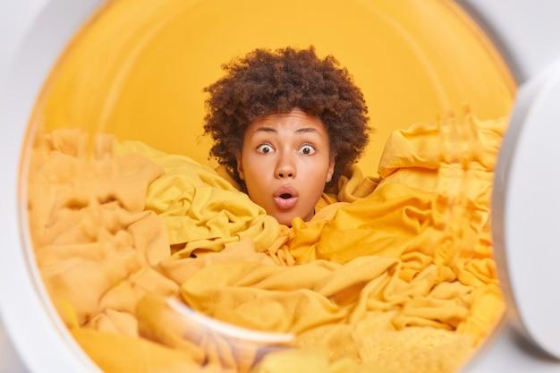 Geschrokken, drukke jonge vrouw met krullend haar, omringd door gele was, laadt vuil linnen en doet huishoudelijke klusjes door de deur van de wasmachine te wassen