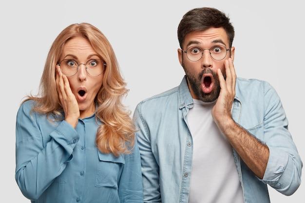 Geschrokken emotioneel familiepaar kijkt met verbazing, verbaasd