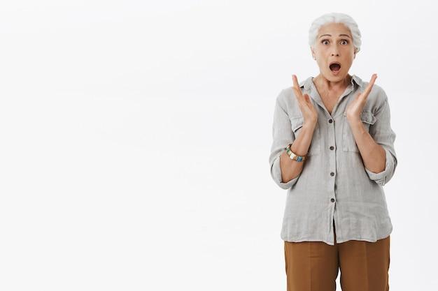 Geschrokken grootmoeder die naar adem snakt en verbaasd kijkt, witte achtergrond