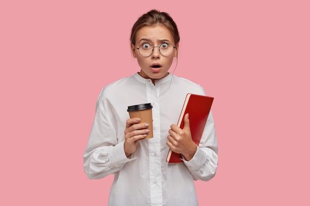 Geschrokken jonge vrouw met bril poseren tegen de roze muur