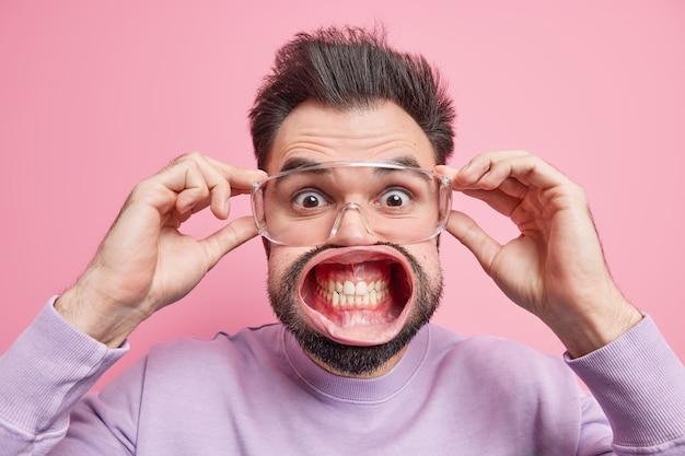 Geschrokken knappe man staart verrassend door transparante bril klemt tanden heeft mond wijd geopend