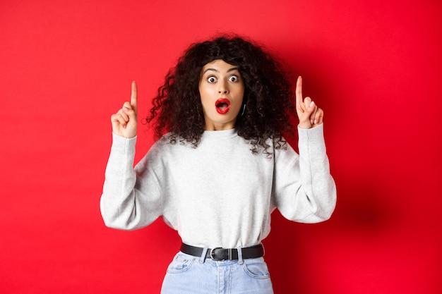 Geschrokken meisje dat geweldig nieuws laat zien, kaak laat vallen en naar adem snakkend verrast terwijl ze met de vingers naar de lege ruimte wijst, in sweatshirt en spijkerbroek op rode achtergrond staat