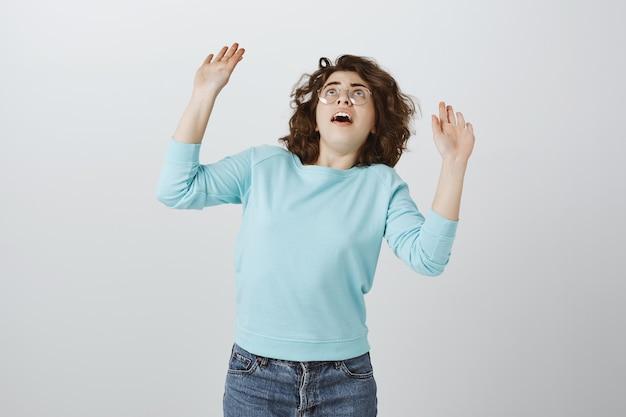 Geschrokken meisje dat zijn handen opheft en staart terwijl er iets op haar valt