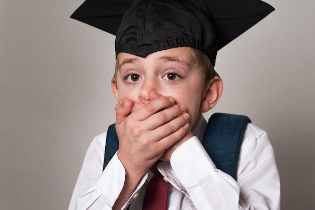Geschrokken schooljongen bedekte zijn mond met handen. jongen in studentenhoed. witte achtergrond. middelbare school.