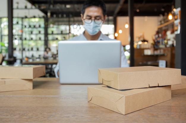 Geselecteerd ocuspakket op tafel met man met medisch maskerwerk op laptop.