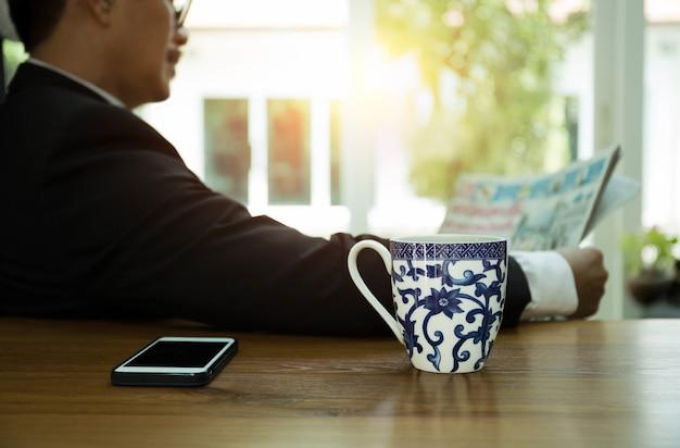 Geselecteerde de koffiemok van de nadrukmok die ontbijt heeft en een krant met cel pone leest