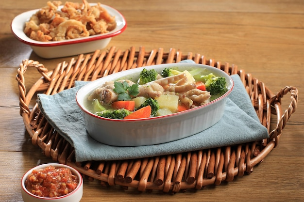 Geselecteerde focus chicken feet (ceker) op heldere groentesoep met aardappel, broccoli en wortelen. geserveerd op houten tafel in ovale kom met sambal. en oesterzwam kopiëren ruimte voor tekst