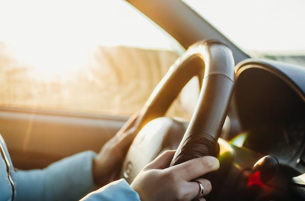 Geselecteerde focus vrouw is handen op het stuur van de auto