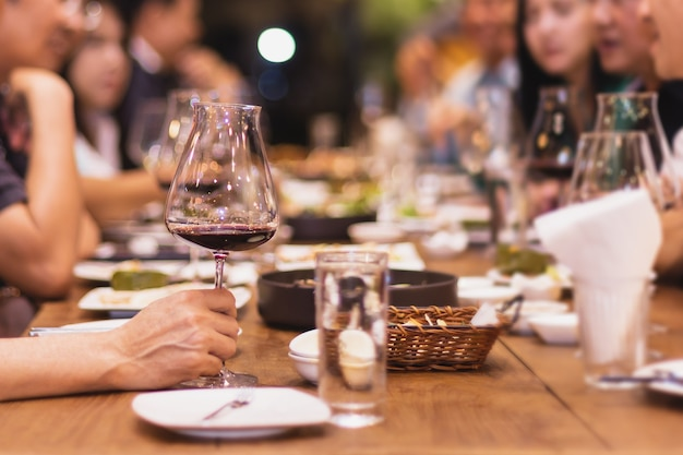 Geselecteerde focusgroep vrienden dineren in restaurant rode wijn drinken binnen