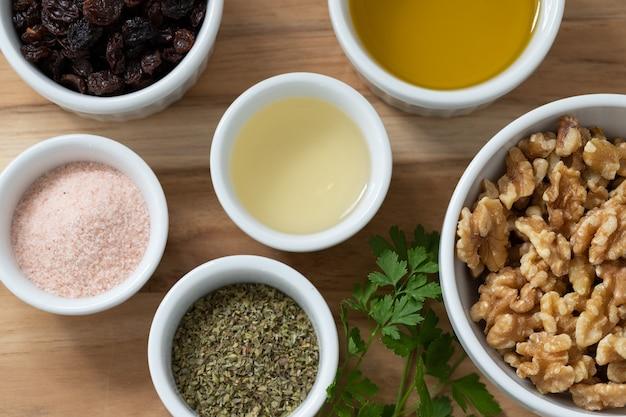 Geselecteerde ingrediënten voor een gezond recept. roze himalayazout, noten, oregano en rozijnen