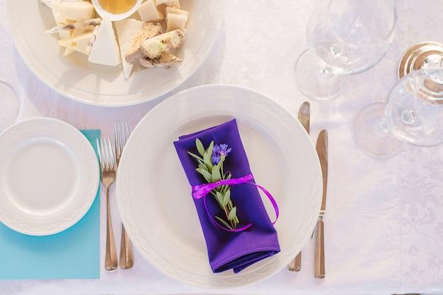 Geserveerd bord met bestek en een fel paars servet met een takje eucalyptus in het decor van een bruiloftsdiner of vakantie