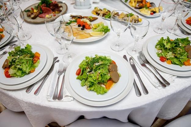 Geserveerd ronde banket tafel met gerechten.