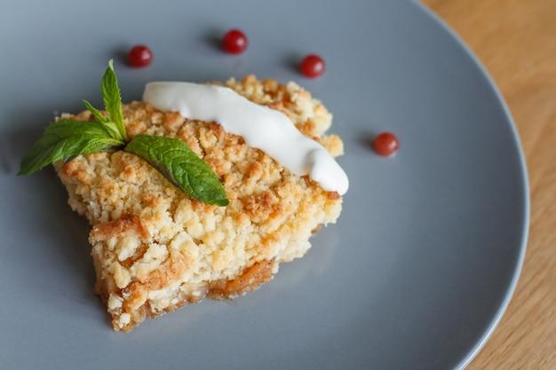 Geserveerd stuk vers gebakken huisgemaakte appel knapperige taart met room en bessen op een grijze plaat