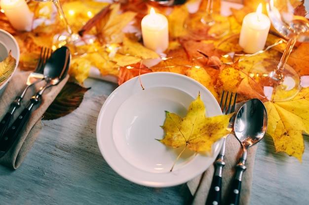 Geserveerd tafel met decoraties, kaarsen en herfstbladeren