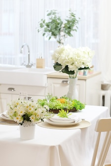 Geserveerde eettafel met een wit tafelkleed, bloemen, glazen en borden. zinken bij het raam.