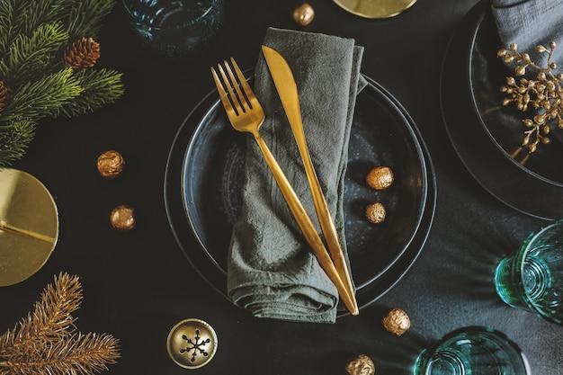 Geserveerde kersttafel in donkere tinten met gouden deco.