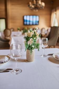 Geserveerde tafel met brandende kaarsen en verse bloemen voor een feestelijk diner.
