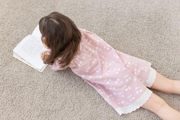 Gesign, baby, mensenconcept - jong meisje dat op de vloer ligt en een boek leest.