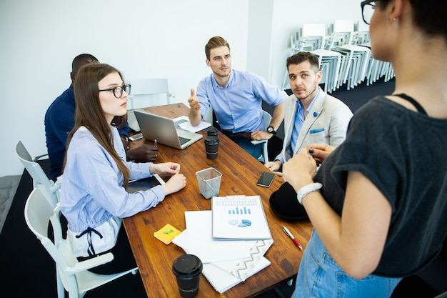 Geslaagd project bespreken. groep jonge vrolijke zakenmensen werken en communiceren zittend aan het bureau samen met collega's op de achtergrond.