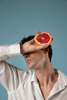 Geslachtsvloeiende persoon met een grapefruit holding