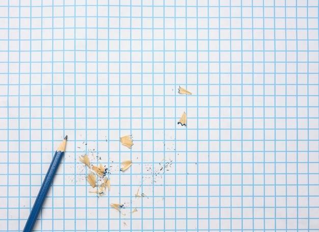 Geslepen houten potlood met schaafsel op een geruit vel papier, kopieer ruimte