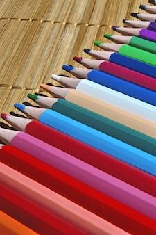 Geslepen veelkleurige potloden op rieten beddengoed.