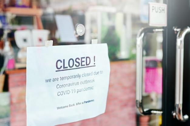 Gesloten aankondiging op deur ingang café restaurant of bedrijfskantoorwinkel is gesloten vanwege het effect van coronavirus covid-19 pandemie, 2e.
