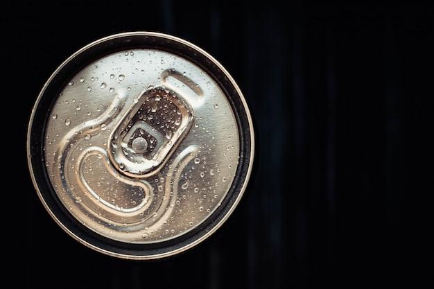 Gesloten blikje cola op zwarte achtergrond. bovenaanzicht