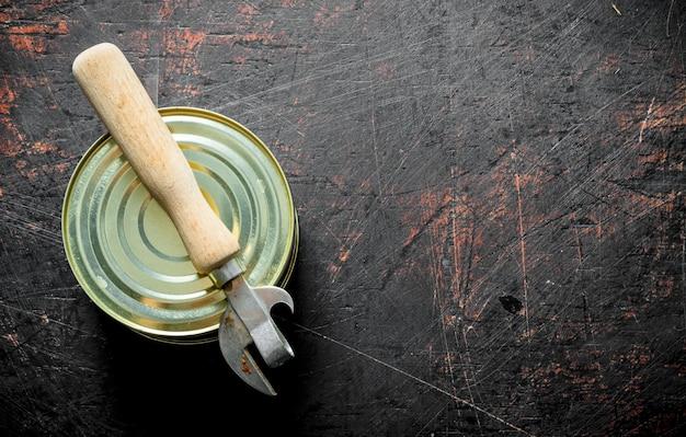 Gesloten blikje met ingeblikt voedsel met een opener op rustieke tafel.