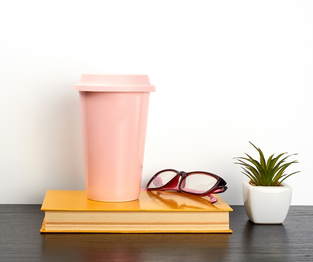 Gesloten boek en roze keramisch glas met koffie op een zwarte tafel