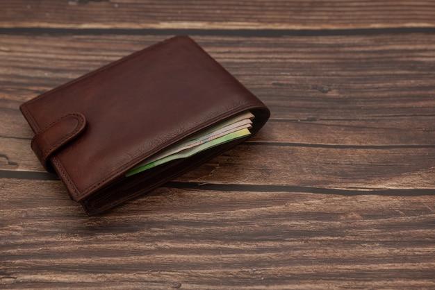 Gesloten bruine portemonnee voor mannen op een houten bruin met geld.