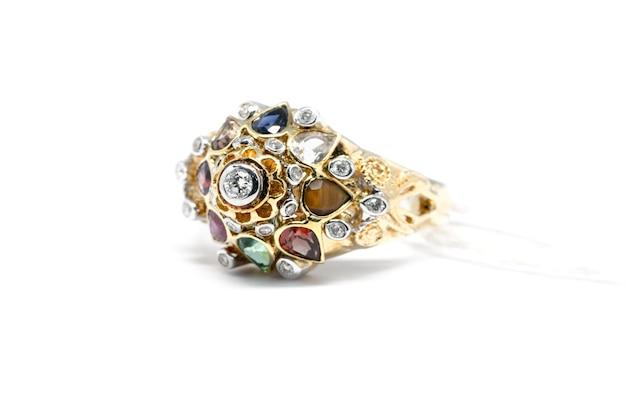 Gesloten emerald, blue sapphire en pink diamond met witte diamant en gouden ring geïsoleerd op wit