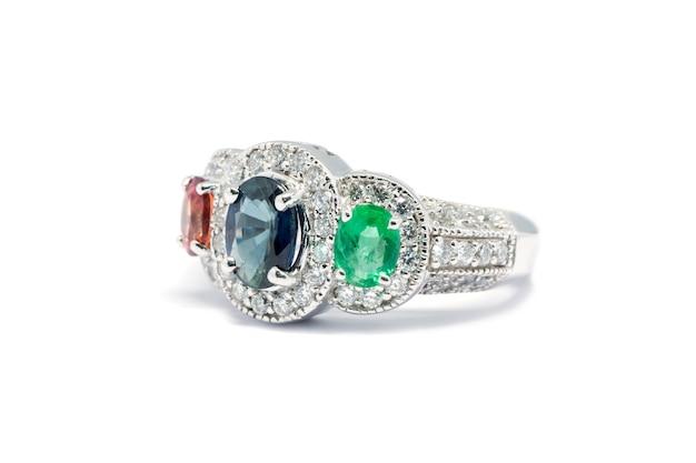 Gesloten emerald, blue sapphire en pink diamond met witte diamant en platina ring geïsoleerd op w