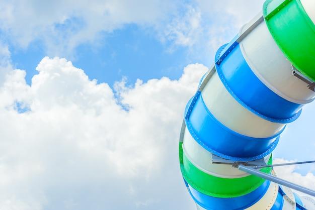 Gesloten gekleurde buisvormige pijpdia bij openluchtwaterpark met duidelijke blauwe hemel.