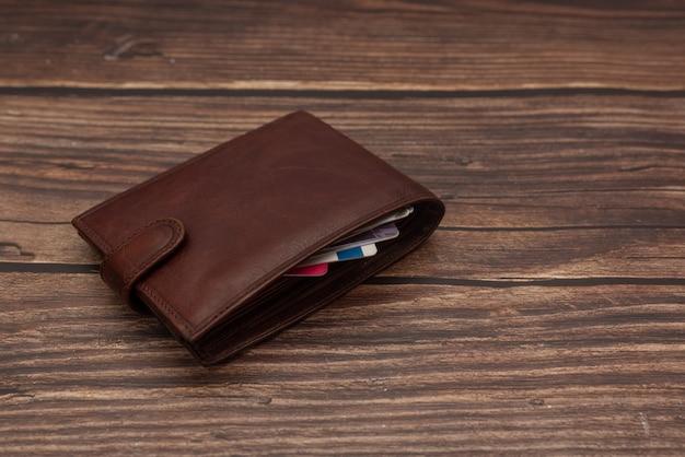 Gesloten heren bruine portemonnee op een houten bruin met visitekaartjes.