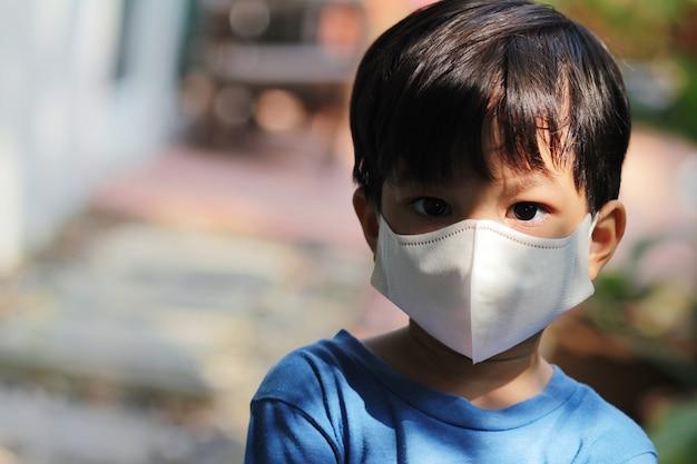Gesloten hoofdschot van jong geitje dat masker draagt. aziatische kleine jongen in corona virusuitbraak en pm 2.5 crisisconcept.