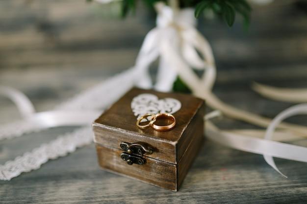 Gesloten houten kistje met een hartje en gouden ringen voor de bruid en bruidegom