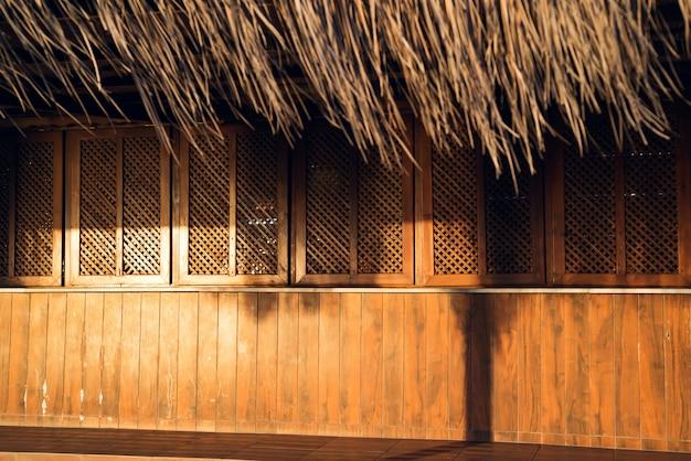 Gesloten houten strandbar met zonsondergangzonlicht